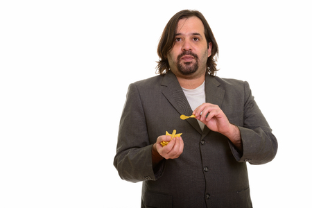 Fat Caucasian businessman eating mouthful of chips