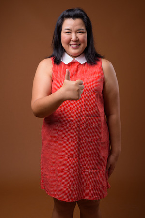 Beautiful overweight Asian woman smiling and giving thumb up