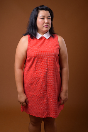 Beautiful overweight Asian woman against brown background