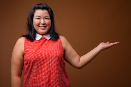 Happy overweight Asian woman showing copy space while smiling