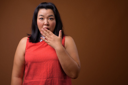 Guilty overweight Asian woman looking shocked and surprised Stock Photo