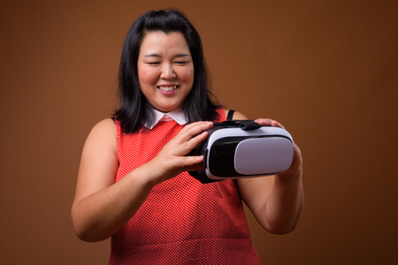 Beautiful overweight Asian woman holding virtual reality VR glasses while smiling