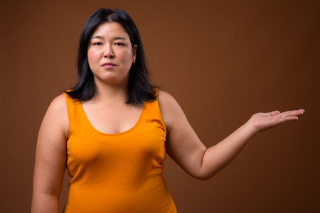 Beautiful overweight Asian woman showing copy space