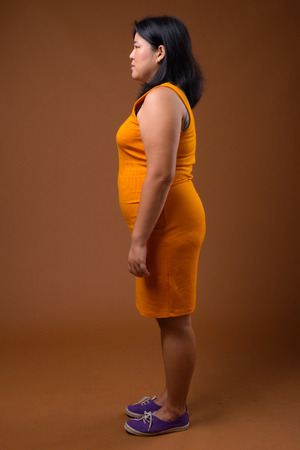 Full length profile view of beautiful overweight Asian woman