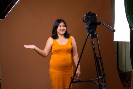 Beautiful overweight woman vlogging in studio with dslr camera on tripod