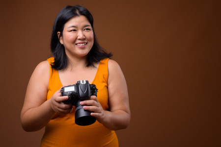 Beautiful overweight Asian woman photographer thinking and planning