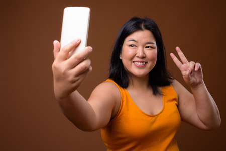 Beautiful overweight Asian woman using mobile phone to take selfie