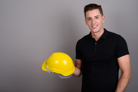 Young handsome man construction worker holding hardhat