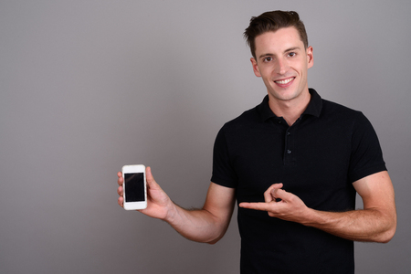 Happy man showing copy space from mobile phone