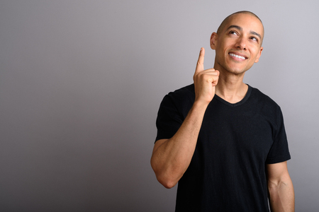 Handsome bald man thinking and pointing finger up