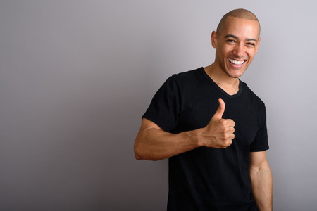 Handsome happy bald man smiling and giving thumb up Фото со стока
