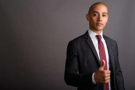 Handsome bald businessman wearing suit and giving thumb up