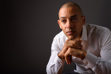 Handsome bald businessman thinking against gray background Banque d'images