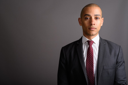 Handsome bald businessman wearing suit against gray background