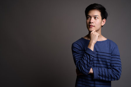 Young handsome Asian man thinking with hand on chin