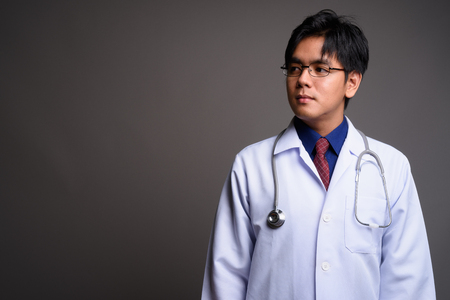Portrait of young Asian man doctor thinking against gray background Stock fotó