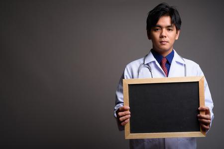 Asian man doctor holding empty blackboard with copyspace