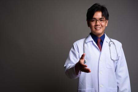 Portrait of happy young Asian man doctor giving handshake