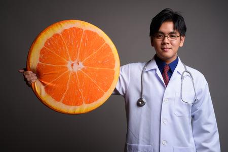 Young Asian man doctor holding big slice of orange fruit Stock fotó