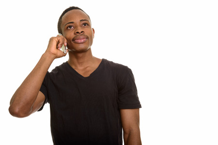 Young African man talking on mobile phone while thinking 免版税图像