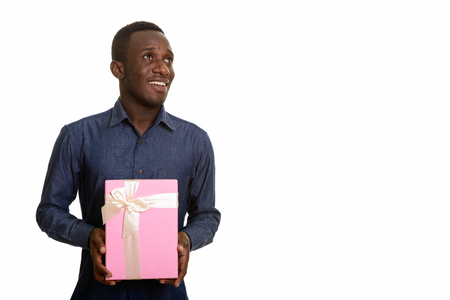 Happy African man smiling and holding gift box while thinking