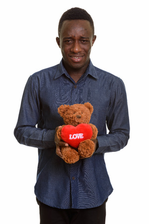 Sad African man holding teddy bear with heart and love sign