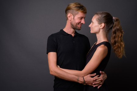 Studio shot of couple together and in love against gray backgrou