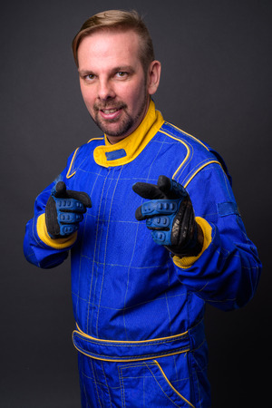 Blond bearded man motorcyclist with goatee in full gear against Stock Photo
