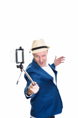Mature businessman holding selfie stick while taking selfie pict