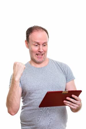 Studio shot of happy mature man smiling while holding digital ta Stock Photo
