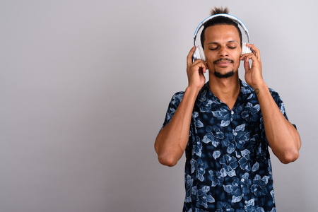 Young bearded handsome African man listening to music against gr