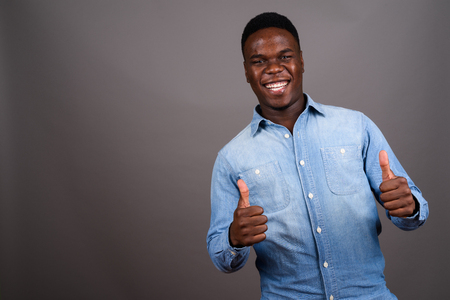 Young African man wearing denim shirt against gray background