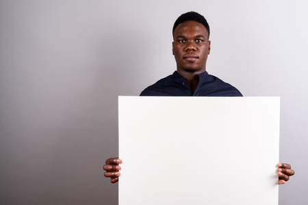 Young African businessman holding white board against white back