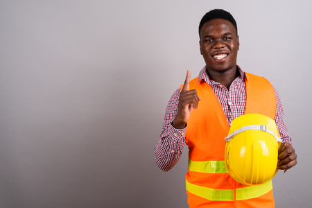 Young African man construction worker against white background