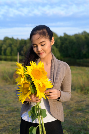 Young beautiful Asian woman holding bouquet of sunflowers against relaxing view of nature Stok Fotoğraf