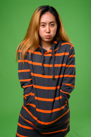 Portrait of young Asian woman against green background Stock Photo