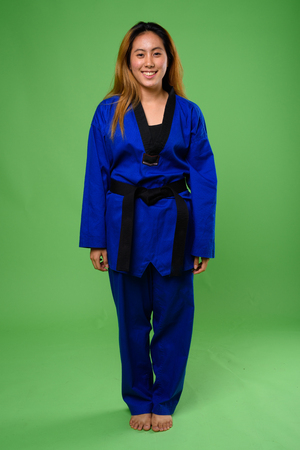 Young Asian woman wearing blue karate Gi against green backgroun