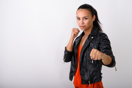 Studio shot of young Asian woman wearing leather jacket ready to
