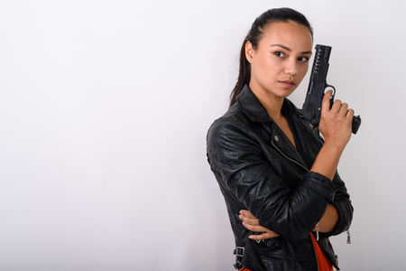 Studio shot of young Asian woman thinking while holding handgun Archivio Fotografico - 111012813
