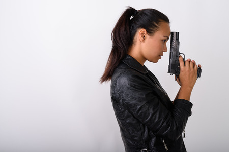 Profile view of young Asian woman holding handgun against white