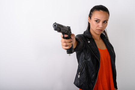 Studio shot of young Asian woman aiming handgun at distance agai