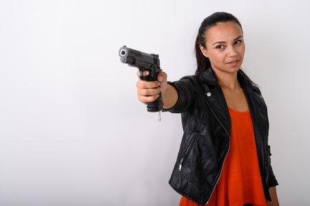Studio shot of young Asian woman aiming handgun at distance read