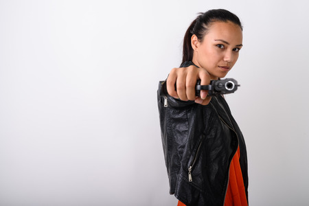 Studio shot of young Asian woman aiming handgun at camera agains Banque d'images