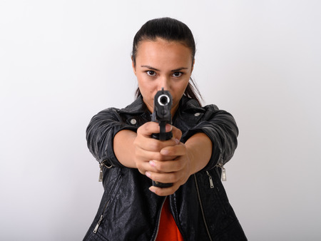 Close up of young Asian woman aiming handgun at camera with both