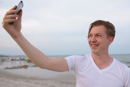 Young happy handsome man smiling while taking selfie picture wit