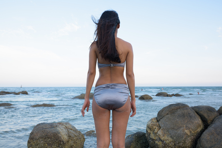 Back view of young beautiful Asian woman standing on the rocks o Banco de Imagens
