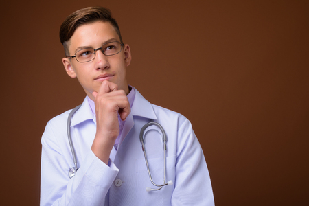 Studio shot of young handsome doctor against brown background Imagens