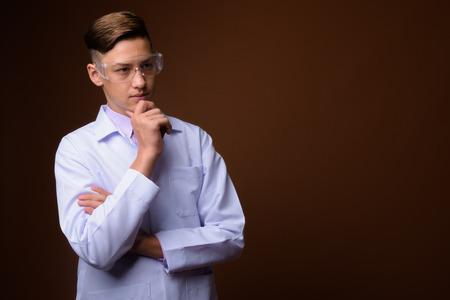 Studio shot of young handsome doctor against brown background Banque d'images