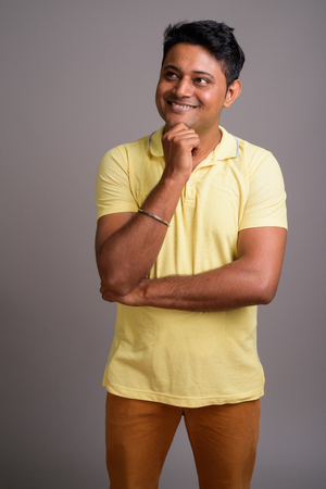 Portrait of young Indian man against gray background