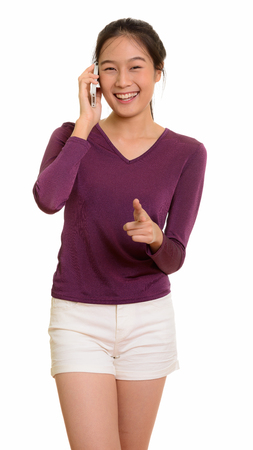 Young happy Asian teenage girl smiling and talking on mobile pho